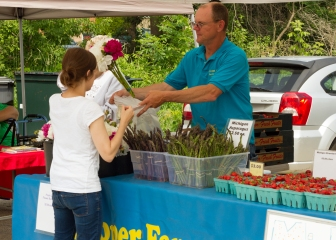 Nicole Knapp, left, buys flowers at the Cooper Farms stand at the Brookfield farmers market.