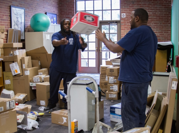 Custodians Tim Riles and Adrian Brown, right, organize boxes at Willard School.